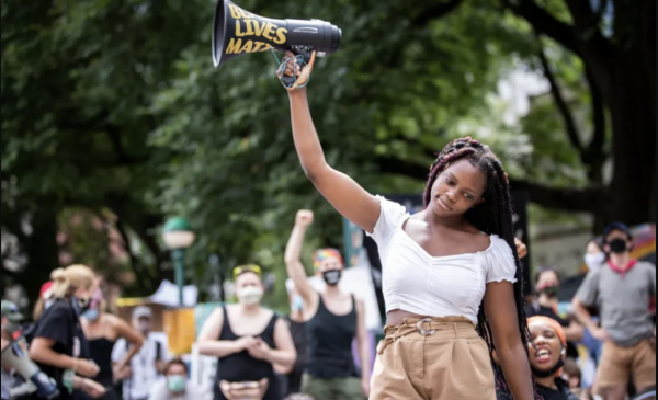 Image of Kiara Williams holds up a megaphone as she talks to the crowd assembled in the Occupy City Hall campgrounds in New York City.